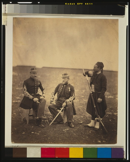 [Two French officers, seated, and Zouave, standing with arm resting on rifle]