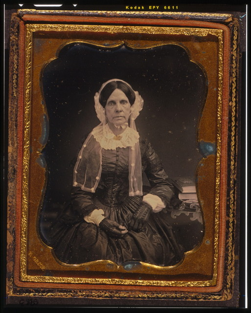 [Unidentified woman, three-quarters length portrait, seated with left arm resting on table with tablecloth and book]