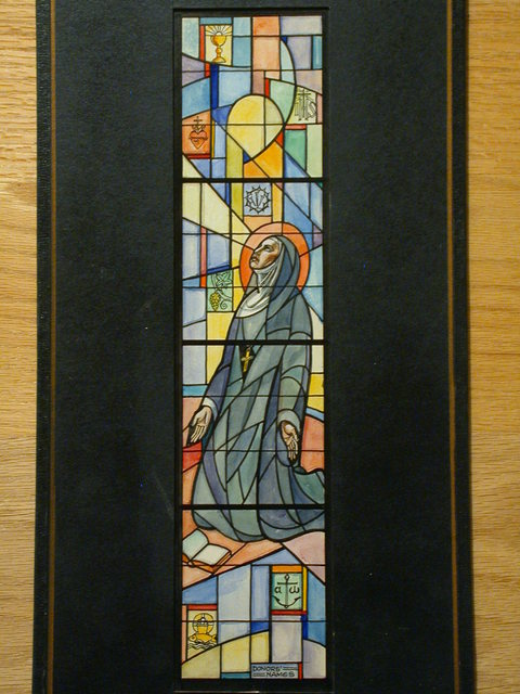 [Design drawing for stained glass window showing Nun in habit praying, with symbols, mid grid]