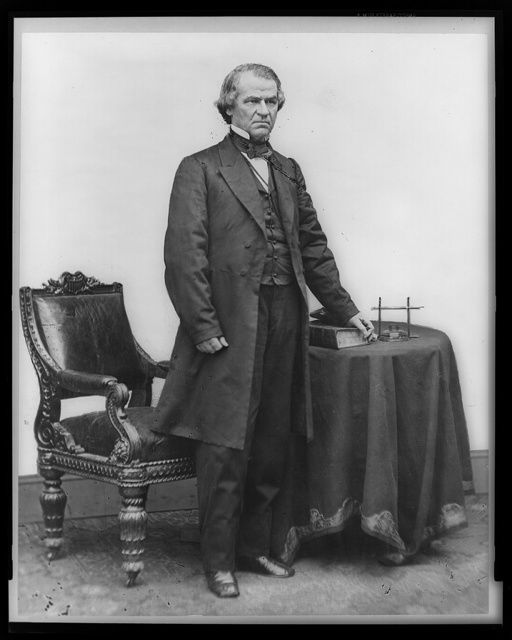 [Andrew Johnson, full-length portrait, standing, facing right, with table and chair]
