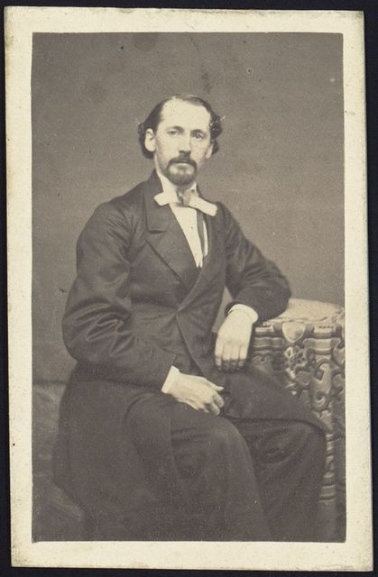 [Archibald Shaver, three-quarter length studio portrait, seated with left arm resting on table, facing front]