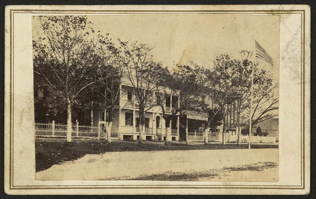 "[Building with sign ""Magnolia Hotel"" and U.S. flag flying out front on the right] / Hubbard & Mix, practical photographers, Beaufort, S.C."