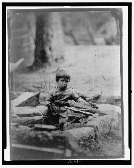 [Full-length portrait of a child sitting amidst rubble]
