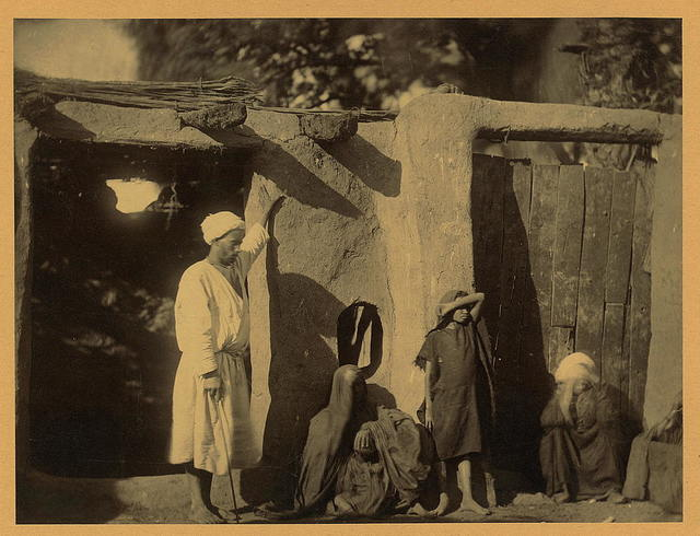 [Man, woman, and children outside earth and wood structure]