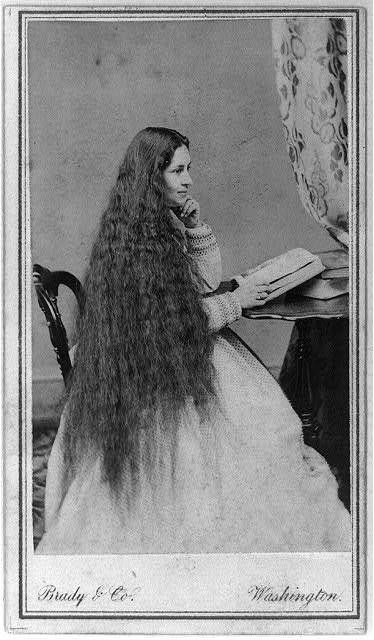 [Mrs. Gen. M. Vickers(?) with long flowing hair, three-quarter length portrait, seated at table with open book]
