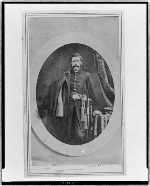 [Orrin J. Crane (?), Union officer, three-quarter length portrait, standing with coat over right shoulder, left hand resting on table, facing front]