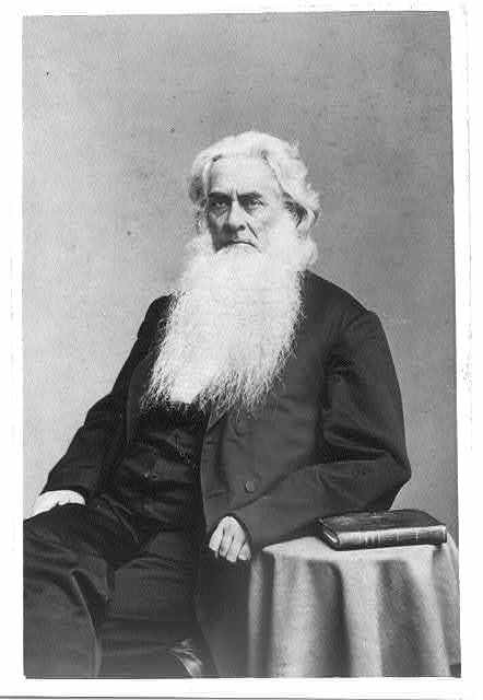 [Rev. Dr. Clifford H. Plumer(?), three-quarter length portrait, seated with left arm resting on small table, facing left]