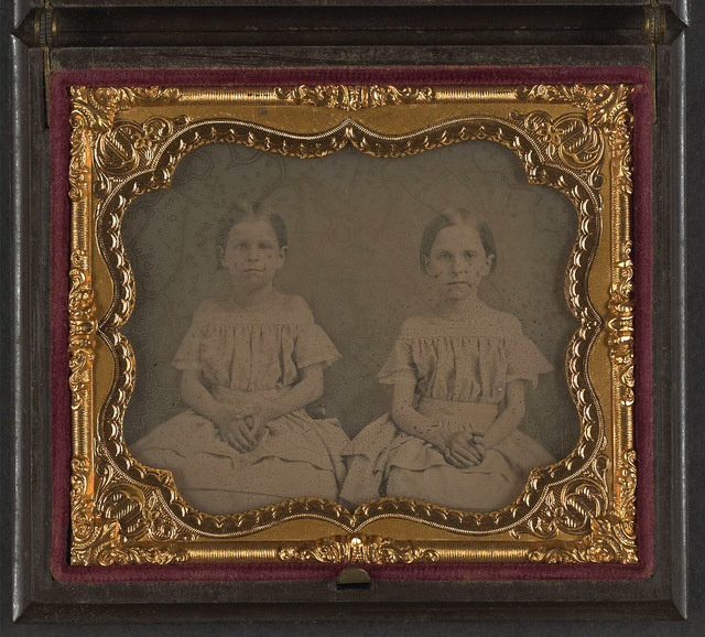 [Two unidentified young girls, probably sisters, wearing matching dresses]