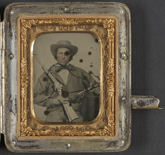 [Unidentified soldier in Confederate cavalry uniform with Sharps carbine, pistol, and knife]