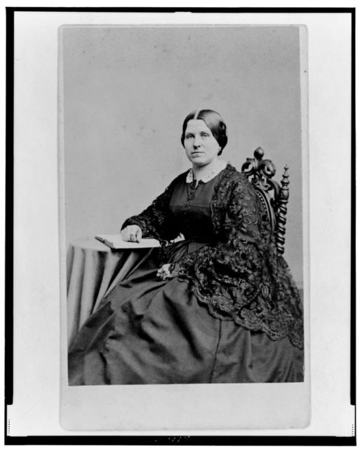 [Unidentified woman, three-quarter length portrait, seated with hand on book, facing left]