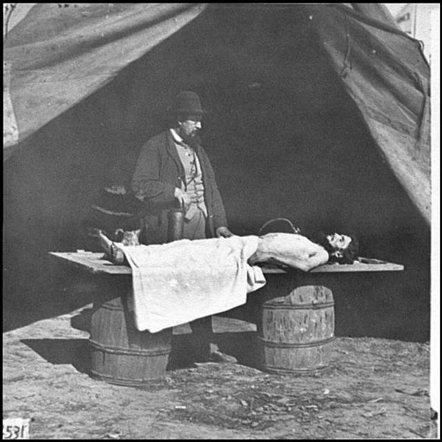 [Unknown location. Embalming surgeon at work on soldier's body]