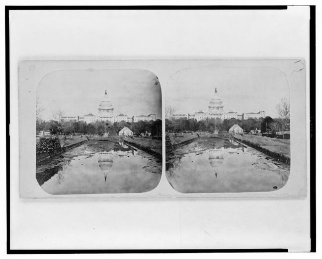 [View from the west of the U.S. Capitol with reflection in body of water in the foreground and the U.S. Botanic Garden in the middle ground]