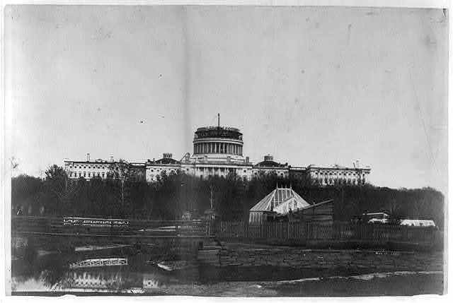 [West front of the United States Capitol, with the new cast-iron dome under construction. In the foregrd. is the Tiber Creek or Washington City Canal and the octagonal greenhouse for the Botanic Garden]
