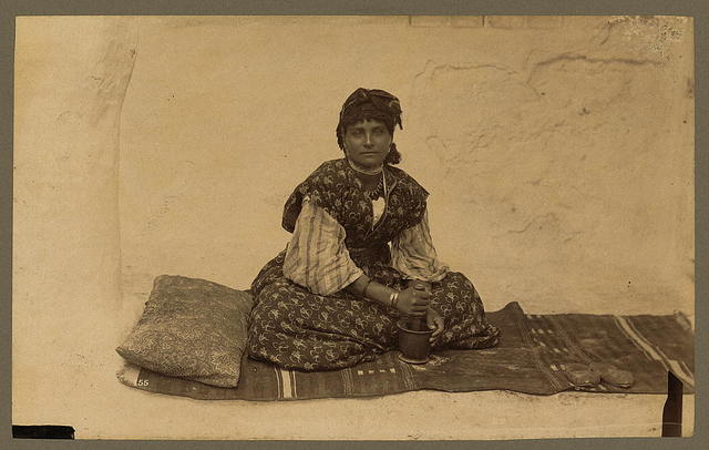 [Woman, full-length portrait, seated on rug on ground, facing front, using mortar and pestle, Constantine, Algeria] / ND.