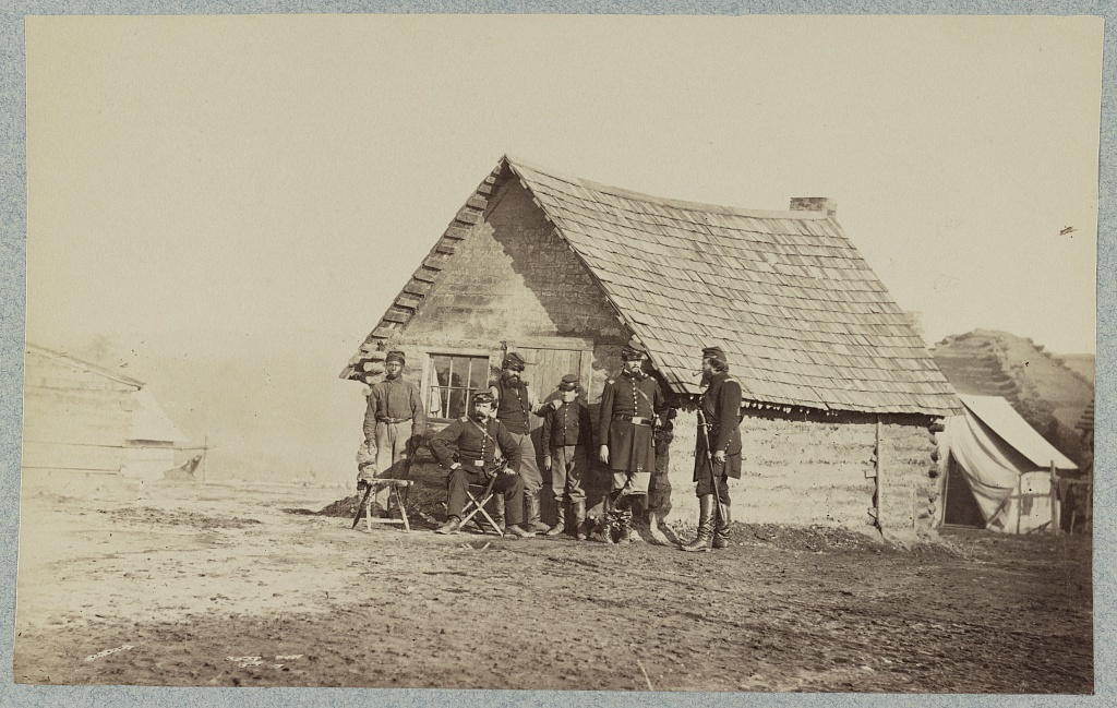 [A group of soldiers, and two young men, one an African American, stand outside of log cabin quarters]