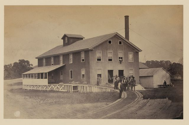 [African American workers standing on railroad tracks in front of a storage facility, possibly at Giesboro cavalry depot]
