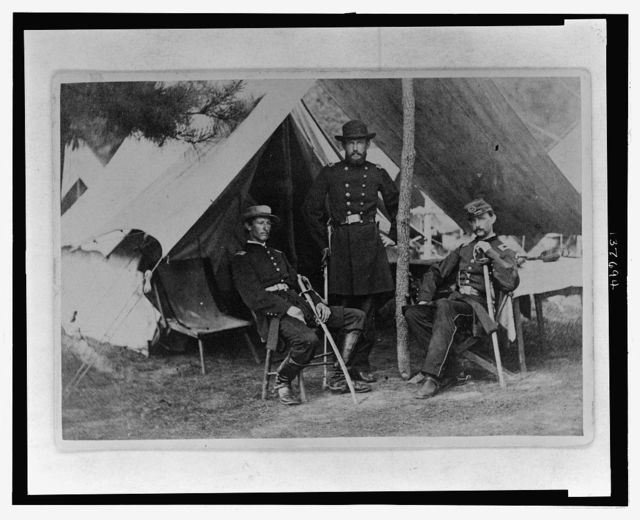 [Albert J. Myer, U.S. Army Signal Corps officer, full-length portrait, facing front, standing under canopy in front of a tent, with one hand on ridge pole, with two men, one sitting on the left and the other sitting on the right]