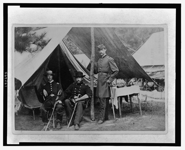 [Albert J. Myer, U.S. Army Signal Corps officer, full-length portrait, facing slightly left, holding sword, sitting under canopy in front of a tent with two men, one sitting on the left and the other standing, holding the ridge pole]