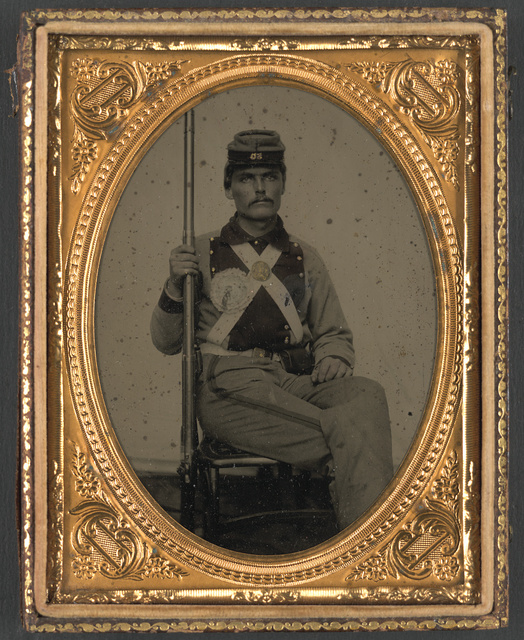 [Corporal John Wesley Edmunds of Co. B, 11th Virginia Infantry Regiment in uniform with secession badge and state seal breastplate holding musket]