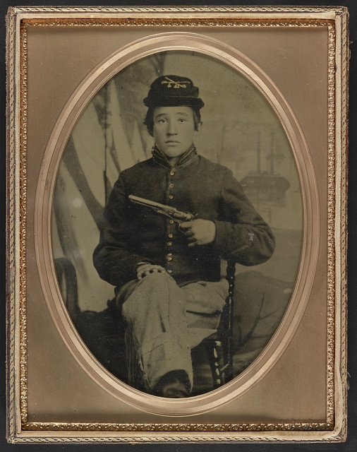 [David Potts in Union cavalry uniform, with revolver, in front of painted background]