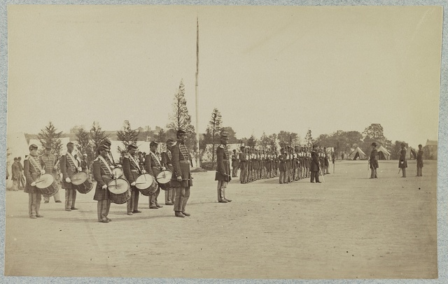 [Drum corps stands in front of Union soldiers in formation]