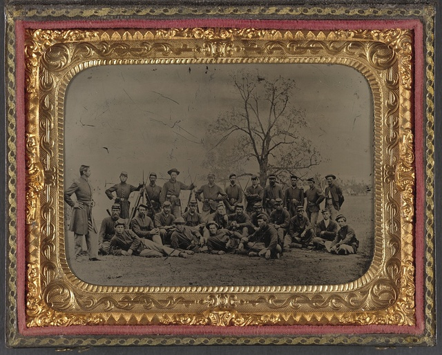 [Group of 26 unidentified soldiers in Union uniforms with stacked bayoneted muskets in front of tree]