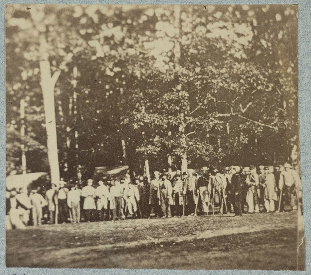 [Group of soldiers, some in uniform and some with crutches, pose in front of the woods at the hospital at Camp Letterman in Gettysburg]