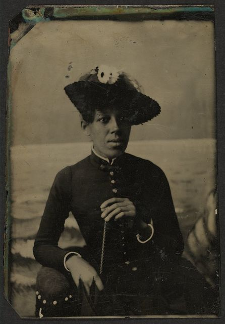[Half-length portrait of an African American woman wearing a hat and holding parasol]