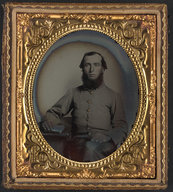 [Joshua Whitten of 45th North Carolina Infantry Regiment seated at a desk with his hand on a book]