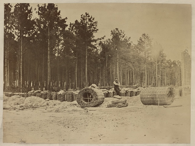 [Man seated on gabions in engineer camp in front of Petersburg, Virginia]