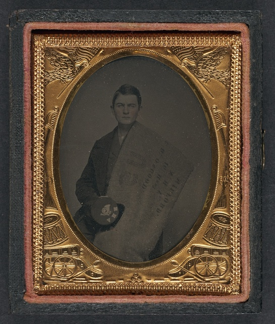 [Private Charles H. Osgood of Company C, 16th New Hampshire Infantry Regiment with stenciled blanket and forage cap]