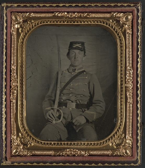 [Private David M. Thatcher of Company B, Berkeley Troop, 1st Virginia Cavalry Regiment, in uniform and Virginia sword belt plate with Adams revolver and cavalry sword]