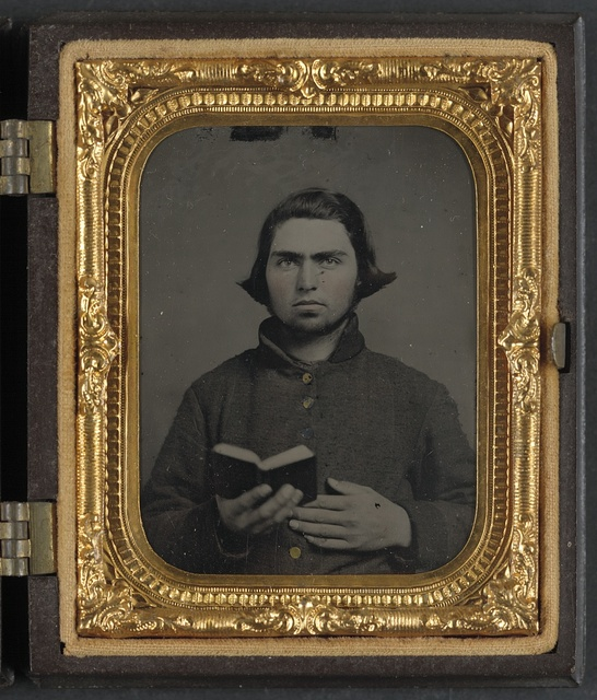 [Private Thomas McCreary of Co. E, 3rd Kentucky Cavalry Regiment, in a Columbus depot jacket and holding a book]