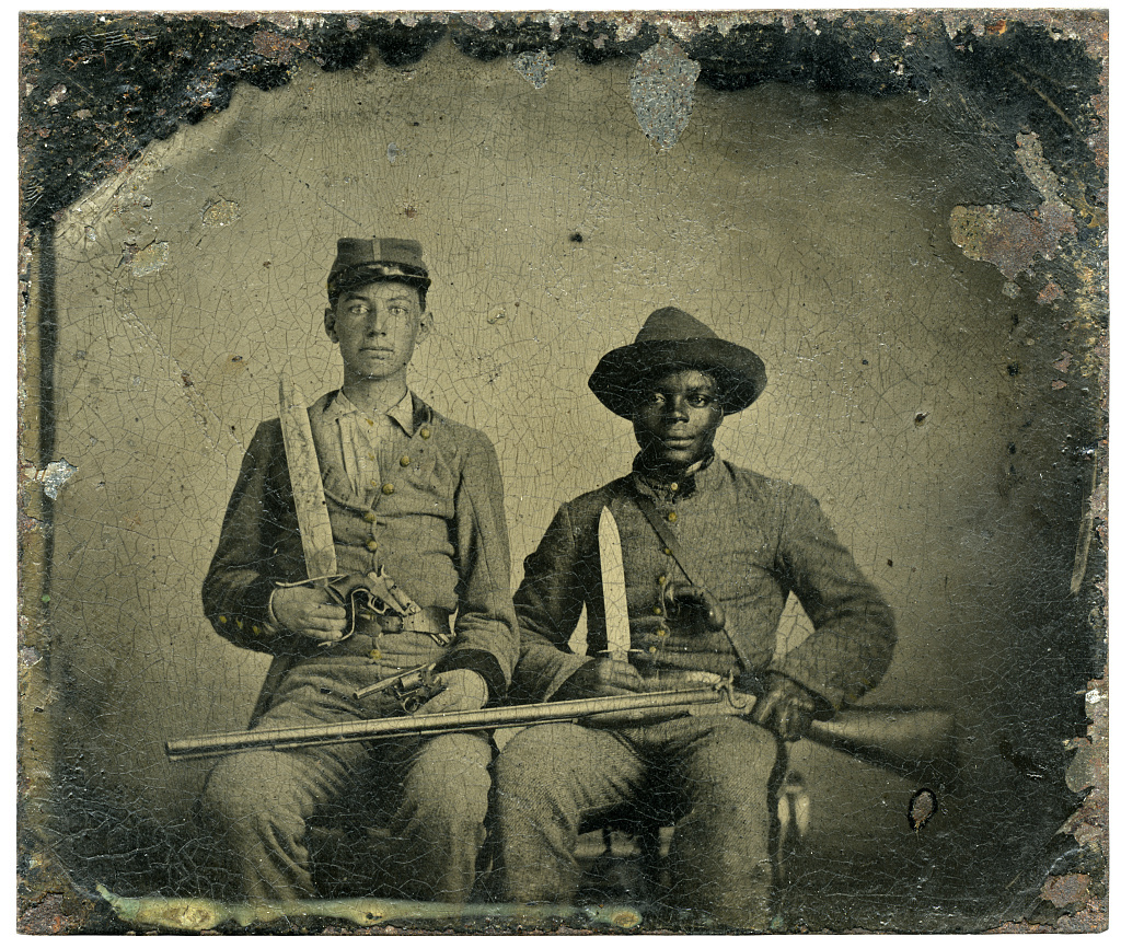 [Sergeant A.M. Chandler of the 44th Mississippi Infantry Regiment, Co. F., and Silas Chandler, family slave, with Bowie knives, revolvers, pepper-box, shotgun, and canteen]