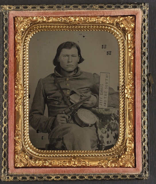 [Thomas Isaiah Booker in Confederate uniform with Colt navy revolver, book, tin drum canteen, and sign reading Jeff Davis and the South!]