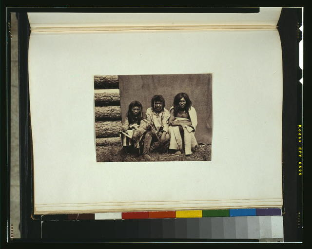 [Three Kootenai men, full-length portrait, seated against blanket in front of a log cabin, facing front, wearing traditional dress]