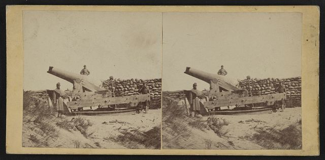 [Three soldiers posing by a mounted cannon with a wall of sandbags behind them]