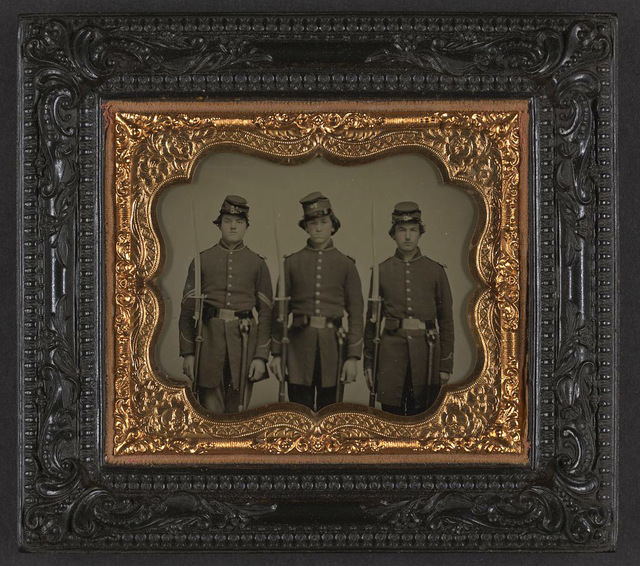 [Three unidentified soldiers in Union uniforms with shoulder scales and cap boxes holding muskets with attached Enfield sword bayonets and scabbards]