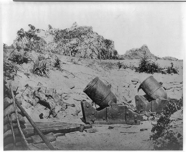 [Two trench mortars behind sandbagged barricade]