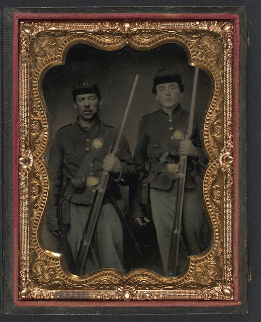 [Two unidentified soldiers in Union shell jackets and forage caps with cartridge pouches, cap boxes, and bayonet scabbards; one soldier in Company C 85th regiment cap; other soldier has holstered pepperbox revolver]