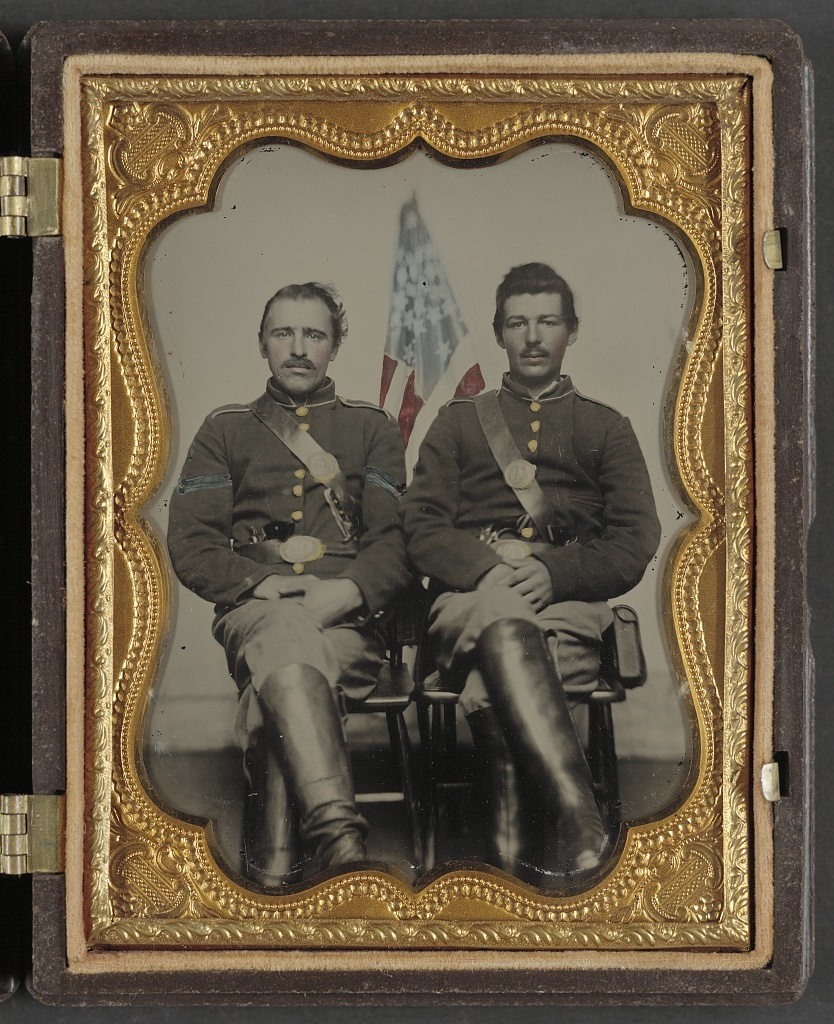 [Two unidentified soldiers in Union uniforms in front of American flag]