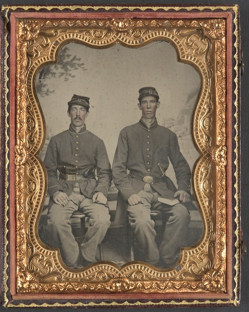 [Two unidentified soldiers in Union uniforms with sword and book in front of painted backdrop]