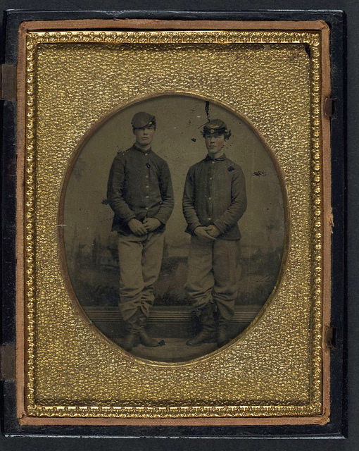 [Two unidentified young soldiers in Union shell jackets and forage caps in front of painted backdrop showing plantation]