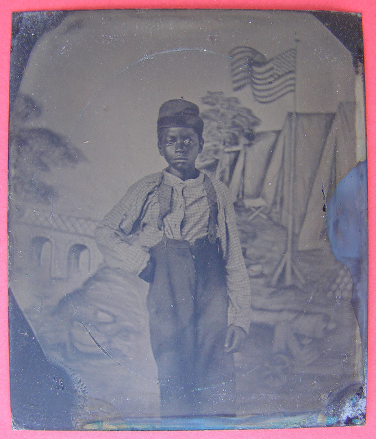 [Unidentified African American boy standing in front of painted backdrop showing American flag and tents ; campaign button with portraits of Lincoln on one side and Johnson on the opposite side are attached to inside cover of case]