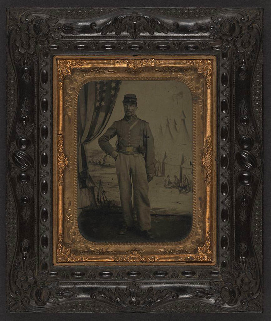 [Unidentified African American soldier in Union artillery shell jacket and shoulder scales in front of painted backdrop showing military camp with flag]