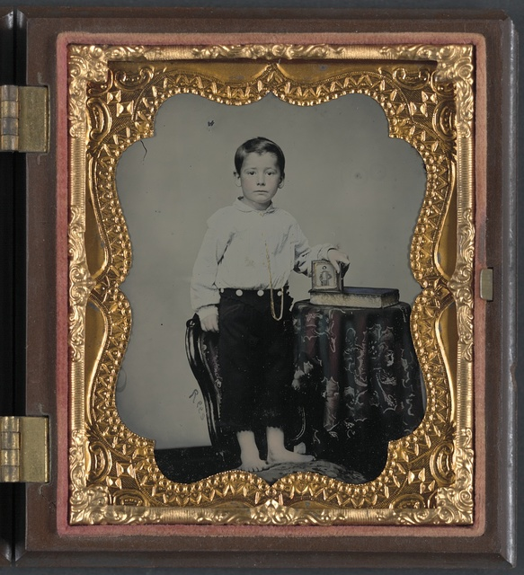 [Unidentified boy holding cased photograph of soldier in Confederate uniform atop a Bible] / Rees.