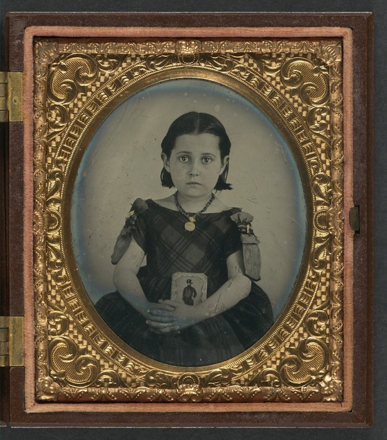 [Unidentified girl in mourning dress holding framed photograph of her father as a cavalryman with sword and Hardee hat]