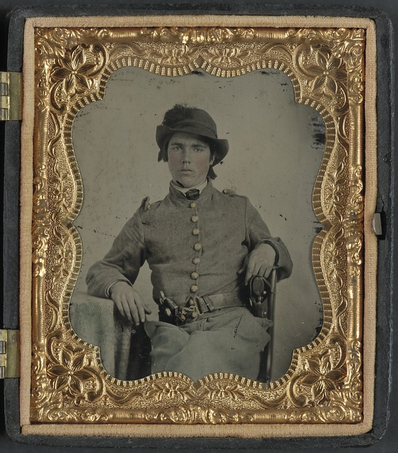 [Unidentified soldier in Confederate cavalry uniform and snake belt buckle with two revolvers]