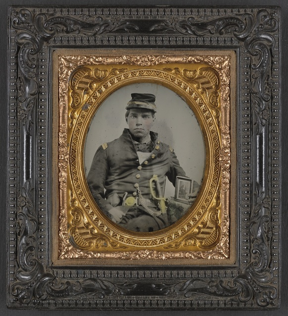 [Unidentified soldier in Confederate officer's uniform with sword and framed photograph]