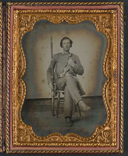 [Unidentified soldier in Confederate uniform with 3-band Enfield rifle and knife]
